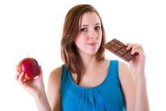 Wahl eines Apfels oder der Schokolade Stockfoto