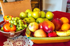Wahl, frische Frucht in drei schönen Schüsseln auf einer roten Tischdecke mit weißer Spitze Stockfotografie