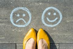 Wahl - glückliche smiley oder unglücklich, Text auf Asphaltstraße Lizenzfreie Stockfotos