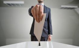 Wahl- und Demokratiekonzept Wähler hält Umschlag oder Papier in der Hand über Stimmzettel Lizenzfreie Stockfotos