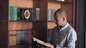 Wahl- und Entscheidungskonzept Mann trifft die Wahl, die in der Bibliothek steht Ein Mann wählt ein Buch zum Ablesen in einer Bib stock video