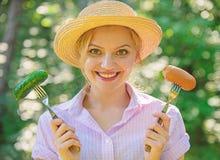 Wahl zwischen Fleisch oder Gemüse Lächelndes Gesicht des Mädchens hält Gabeln mit Wurst und Gurke Alternative Nahrung für stockbilder