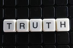 Wahrheitstext-Wortkreuzworträtsel Alphabetbuchstabe blockiert Spielbeschaffenheitshintergrund Schwarzer Hintergrund Lizenzfreies Stockfoto