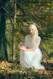 Wahrsagerfrau, die im Wald sitzt Lizenzfreie Stockfotografie