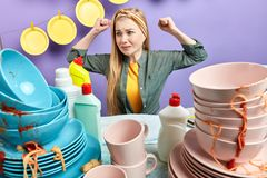 Waht dirty plates.upset caucasian woman looks with dissatisfcation at messy table. Feds up of washing cutlery royalty free stock photos