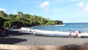 Maui, Hawaii - circa 2013: Tourists visit the Waianapanapa black sand beach. Waianapanapa Beach, Hawaii - circa 2013: Tourists visit the black sand beach at stock video footage