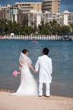 Waikiki Beach - Hawaii wedding. Beautiful bride and groom pose for wedding pictures along Waikiki beach along the beautiful Hawaiian Hilton Village Royalty Free Stock Image