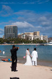 Waikiki Beach - Hawaii wedding. Beautiful bride and groom pose for wedding pictures along Waikiki beach along the beautiful Hawaiian Hilton Village Royalty Free Stock Image