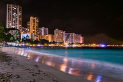 Waikiki beach at night. With Diamond Head in the distance and a nice reflection of the hotels on the wet sand Stock Photography