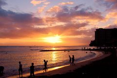 Waikiki Beach Sunset. This is an early Spring sunset on the west shore of Oahu from Waikiki Beach.  I love the way the people seem to be taking in the last rays Stock Photography