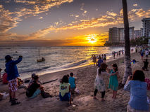 Waikiki beach at sunset. WAIKIKI, HI - APRIL 27 - Tourists on the beach front at sunset on Waikiki beach April 27, 2014 in Oahu. Waikiki beach is beachfront royalty free stock images