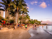 Waikiki beach at sunset. WAIKIKI, HI - APRIL 27 - Tourists on the beach front at sunset on Waikiki beach April 27, 2014 in Oahu. Waikiki beach is beachfront royalty free stock image
