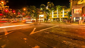 Waikiki city crossroad. HONOLULU, OAHU, HAWAII, USA - AUGUST 21, 2016: Time lapse at night of a Waikiki crossroad. People moving for shopping and car crossing stock footage