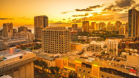 Waikiki city sunset. Aerial view sunset of Waikiki skyline in Oahu island United States. Sun setting to dark sky with moving clouds and stars. City night lights stock footage
