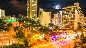 Waikiki moonlight Aerial View. Moonlight Time lapse of night traffic of Waikiki city in Oahu, Hawaii, United States. Moving people and car glowing trails in the stock footage