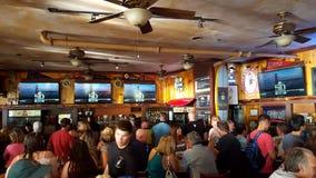 Crowd People watch Superbowl game at iconic Lulu& x27;s Bar. WAIKIKI, OAHU - FEBRUARY 7: Crowd People watch Superbowl 50 game at iconic Lulu& x27;s Bar stock photography