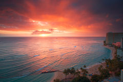 Waikiki resort sunset. Spectacular glowing sunset over turquoise blue water surrounded by high rise resort hotels with surfers from view of Waikiki Beach in Royalty Free Stock Images