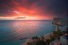 Waikiki resort sunset. Spectacular glowing sunset over turquoise blue water surrounded by high rise resort hotels with surfers from view of Waikiki Beach in Stock Photo