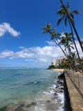 Waikiki riega como las ondas se estrellan en la pared de mar en el parque de la playa de Makalei Imagen de archivo