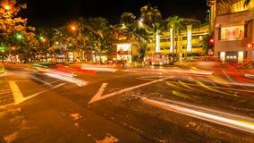 Waikiki street lights. HONOLULU, OAHU, HAWAII, USA - AUGUST 21, 2016: cars crossing the Kalakaua Ave and Seaside Ave crossroad in motion blur with streets lights Royalty Free Stock Photography