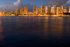 Waikiki Sunset. Lights from luxury hotels reflect in the surf of the Pacific Ocean at dusk in Waikiki, Honolulu, Oahu, Hawaii, USA stock image