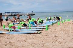 Waikiki surf lessons. Students observe native Hawaiian surf instructor teach the way of the surfboard on Waikiki beach, Hawaii Stock Image
