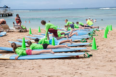Waikiki surf lessons. Students observe native Hawaiian surf instructor teach the way of the surfboard on Waikiki beach, Hawaii Royalty Free Stock Photos