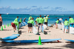Waikiki surf lessons. Students observe native Hawaiian surf instructor teach the way of the surfboard on Waikiki beach, Hawaii Stock Photo