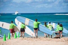 Waikiki surf lessons. Students observe native Hawaiian surf instructor teach the way of the surfboard on Waikiki beach, Hawaii Royalty Free Stock Image