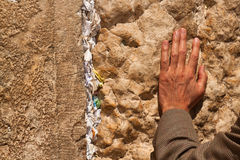 Wailing Wall in Jerusalem. Hand man praying at the Wailing Wall with notes in the wall with requests Royalty Free Stock Photos