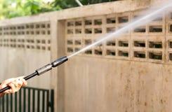 Waill de nettoyage de femme avec le jet d'eau à haute pression photos stock