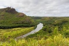 Floden som flödar till och med ett frodigt, landskap Arkivbilder
