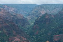 Waimea Canyon on Kauai, Hawaii, in winter after a major rainstorm. The dirt is all soaked and has the deep rich red coloring Royalty Free Stock Images