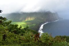 Waimea Valley Hawaii Overlook Foggy view of Coast. Heavy cloud cover of fertile utopian paradise valley from top of mountain with. Mountains in the distance royalty free stock image