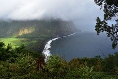 Waimea Valley Hawaii Overlook Foggy view of Coast. Heavy cloud cover of fertile utopian paradise valley from top of mountain with. Mountains in the distance royalty free stock photography