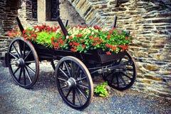 Wain de madeira do vintage decorado com o gerânio vermelho de florescência imagem de stock royalty free
