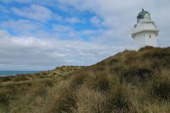 Waipapa Point Lighthouse with dunes and cloudy sky stock photo