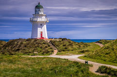 Waipapa Point Lighthouse New Zealand. View of lighthouse on hill at Waipapa Point on New Zealand`s South Island on a cloudy day Stock Images
