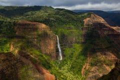 Waipoo понижается в каньон Waimea в ярких зеленых цветах и красные цветы на стоковое фото rf