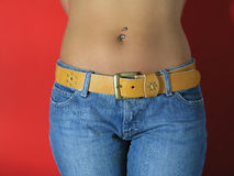 Waist. Girl in Jeans, red background, piercing royalty free stock photography