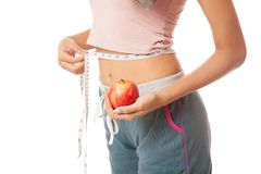 Waist of Asian healthy girl with measuring tape and apple Stock Image