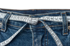 Waist check and excess weight control concept. Pair of blue jeans with measuring tape as belt having tied knot stock photo