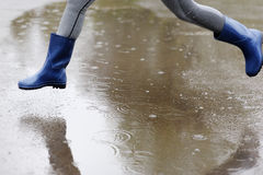 Waist down view of girl jumping puddles on rainy street. Stock Photography