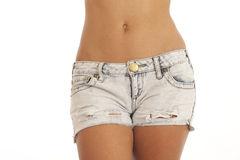 Waist and hips of young woman wearing shorts. Waist and hips of young woman wearing jean shorts Royalty Free Stock Photo