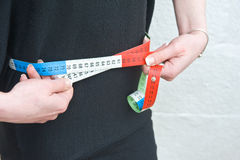 Waist measurement. Slimming ?. A closeup  image of a woman measuring her waist using a multicolored tape measure Royalty Free Stock Image