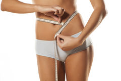 Waist measuring. Pretty girl in panties measure her waist with a tape Stock Photography