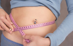 Waist measuring. Young woman measuring her waist with pink tape Royalty Free Stock Photos