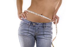 Waist and meauring tape. Woman measuring her waist wearing blue jeans Stock Images