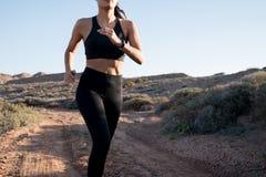 Waist shot of a female runner in the desert stock image