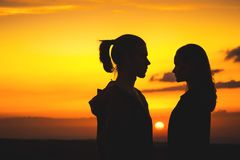 Waist silhouettes of a young millenial couple in love with a man and a girl look at each other. Two profile of a young. Couple at sunset stock image